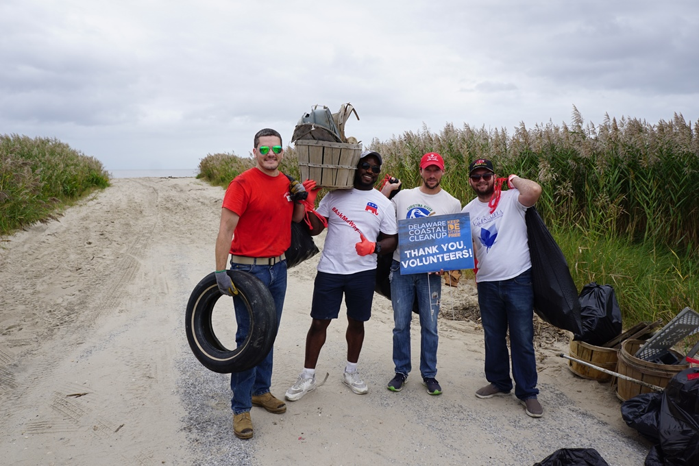 A group of men holding trash they have collected