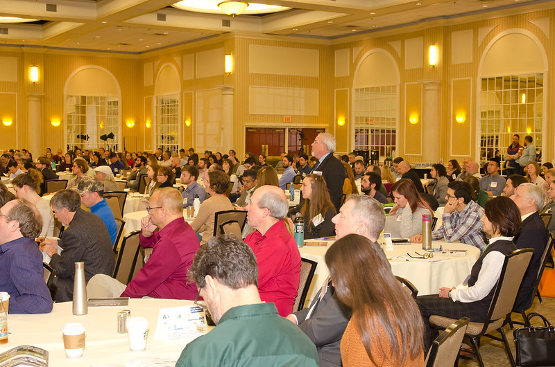 A crowd listens to a speaker at a conference