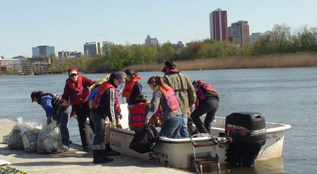 volunteers unload trash from a boat on a river
