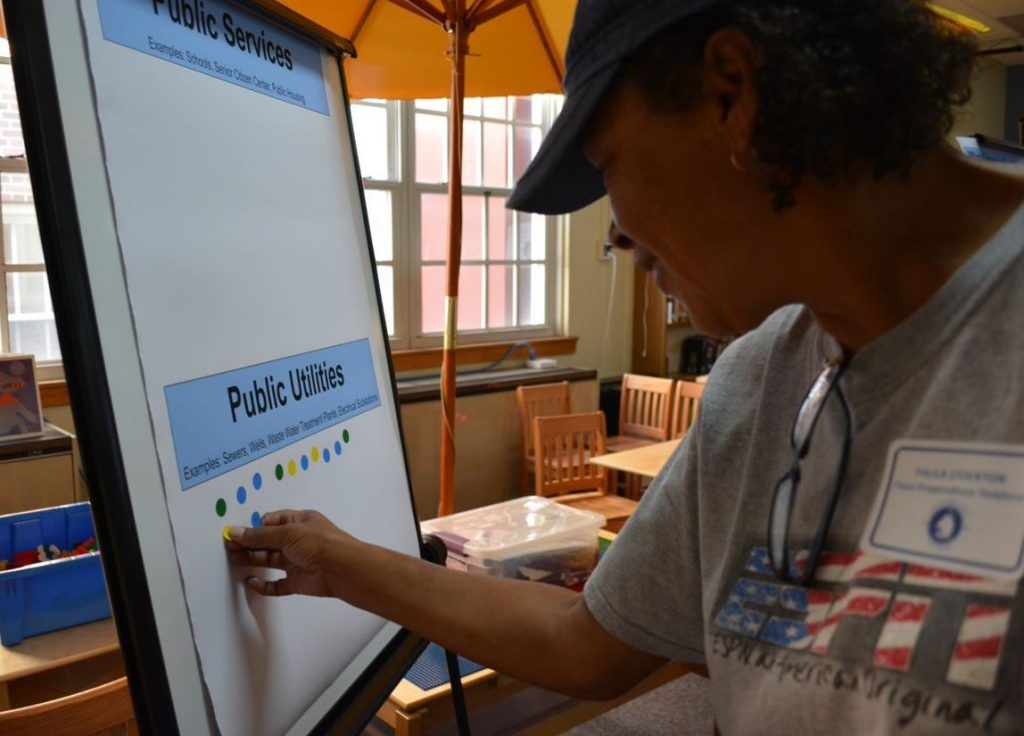 Citizens place markers on a board to vote on issues in a public workshop