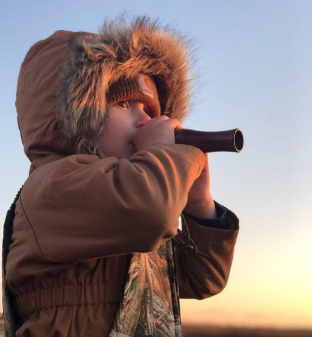A child uses a duck call