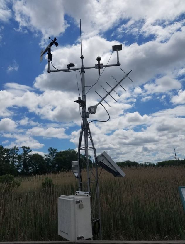 A collection of weather-re;ated instruments are mounted near a marsh