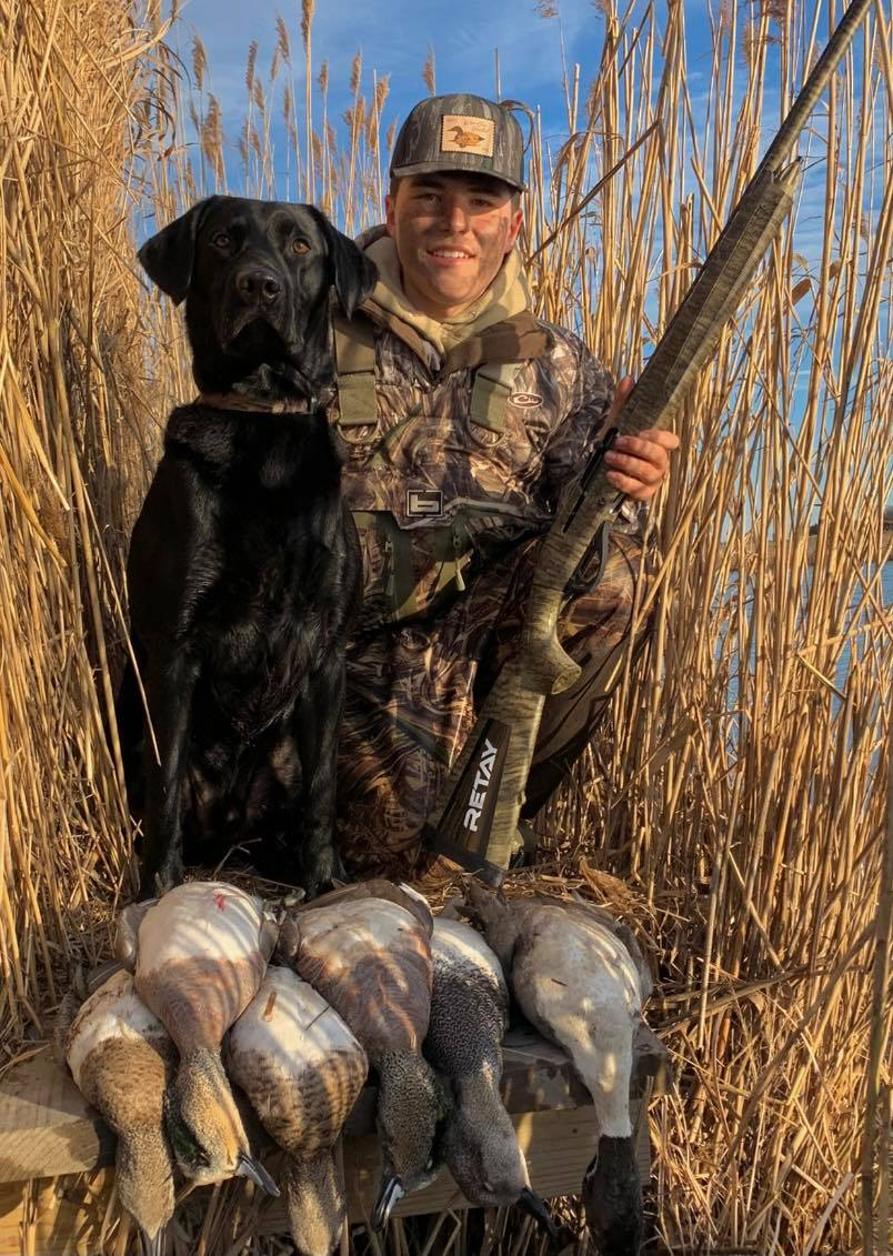 A young hunter poses with his dog and his harvest of waterfowl